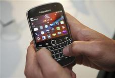Мужчина держит смартфон Blackberry Bold 9900 в Торонто, 3 августа 2011 года. Research In Motion сообщила о резком падении квартальной прибыли на фоне слабых продаж смартфонов и планшетников. REUTERS/Mark Blinch