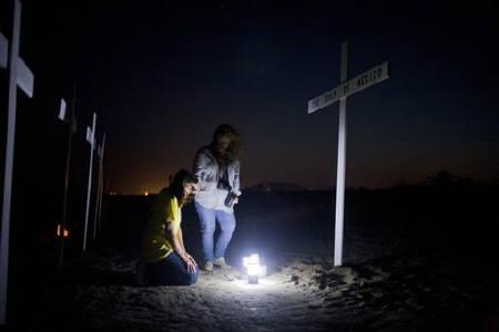 Darlene Eschete (L) and Susan Price gather around a cross honoring the workers who died on the Deepwater Horizon oil platform, during a service marking the one-year anniversary of the BP oil spill, in Grand Isle, Louisiana April 20, 2011.REUTERS/Lee Celano/Files