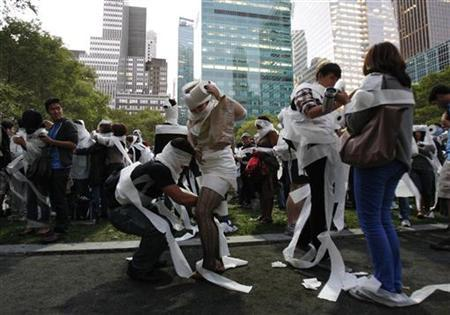 People wrap each other in toilet paper as they take part in the Mp3 Experiment in New York's Bryant Park October 2, 2010. REUTERS/Jessica Rinaldi