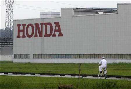 A worker rides a bicycle past a Honda auto parts manufacturing plant in Foshan, Guangdong province June 2, 2010. REUTERS/Stringer