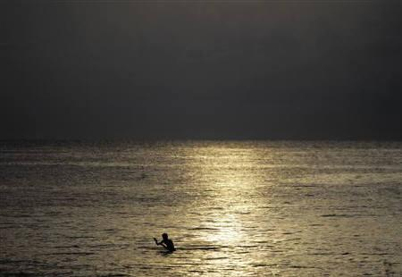A man holds a fishing line in the Atlantic ocean in Havana September 2, 2011. REUTERS/Desmond Boylan/Files