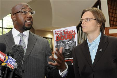 Ebenezer Baptist church Pastor Raphael Warnock (L) speaks next to Amnesty International campaign director Laura Moye during a news conference after the Georgia Board of Pardons and Paroles denied clemency for convicted killer Troy Davis in Atlanta, Georgia September 20, 2011. REUTERS/Tami Chappell