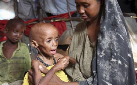 An internally displaced Somali woman holds her malnourished child inside their temporary home in Hodan district, south of Somalia's capital Mogadishu, September 20, 2011. REUTERS/Feisal Omar