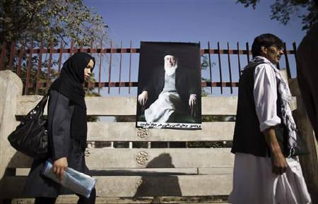 People walk past a picture of Burhanuddin Rabbani, former Afghan president and head of the government's peace council, along a street outside his house, a day after he was killed in Kabul September 21, 2011. REUTERS/Ahmad Masood