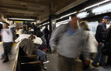A homeless man sleeps on a subway bench during the morning rush hour in New York September 20, 2011. REUTERS/Lucas Jackson