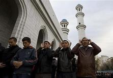 Мужчины молятся около главной мечети в Алма-Ате, 16 ноября 2010 года. Нижняя палата парламента Казахстана в среду одобрила два законопроекта, ужесточающих контроль за духовной деятельностью в преимущественно мусульманской стране, признавшей религиозный экстремизм угрозой своей стабильности. REUTERS/Shamil Zhumatov