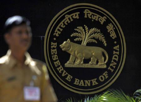 A policeman walks past the logo of the Reserve Bank of India (RBI) outside its head office in Mumbai November 2, 2010. REUTERS/Danish Siddiqui/Files