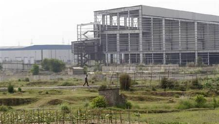A private security guard walks outside the closed Tata Motors Nano car factory in Singur, north of Kolkata, April 27, 2011. REUTERS/Rupak De Chowdhuri/Files