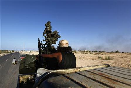 Forces loyal to Libya's interim rulers fire heavy machine guns as smoke rises from Muammar Gaddafi's hometown Sirte September 24, 2011. REUTERS/Anis Mili