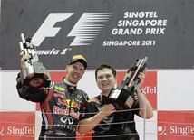 Sebastian Vettel (esquerda), da Red Bull, levanta troféu do Grande Prêmio de Cingapura ao lado do engenheiro da Red Bull Tim Maylon. 25/09/2011 REUTERS/Tim Chong