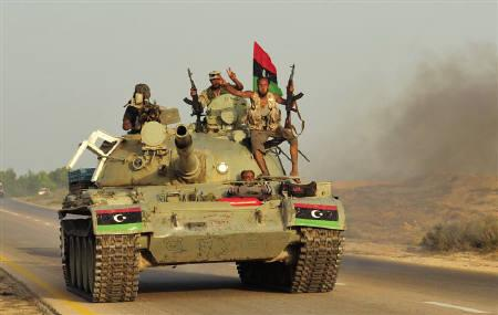 Anti-Gaddafi fighters travel in a tank as they move forward towards Sirte from Talatheen area, 30 km (19 miles) east of Sirte September 25, 2011. REUTERS/Esam Al-Fetori