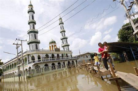 A resident carries her daughter as she walks on a makeshift walkway along flooded streets, at a mosque in Ayutthaya province September 20, 2011. REUTERS/Sukree Sukplang