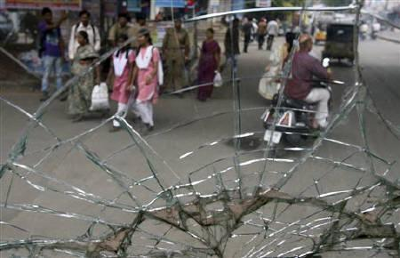 Commuters are seen through a broken window pane of a passenger bus damaged by protesters during a strike demanding statehood for Telangana, in Hyderabad September 16, 2011. REUTERS/Krishnendu Halder/Files