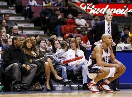 Jay-Z and Beyonce (L) sit court-side and watch the New Jersey Nets play the Indiana Pacers in their NBA game in East Rutherford, New Jersey, January 16, 2006. REUTERS/Ray Stubblebine