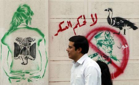 A man walks past a graffiti depicting Field Marshal Mohamed Tantawi, the head of the ruling Supreme Council of the Armed Forces (SCAF), in downtown Cairo, September 23, 2011. The writing on the wall reads: ''No to Military Rule''(top) and ''Donkey''. REUTERS/Amr Abdallah Dalsh