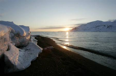 The sun shines low in the sky just after midnight over a frozen coastline near the Norwegian Arctic town of Longyearbyen, April 26, 2007. REUTERS/Francois Lenoir/Files