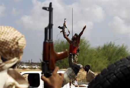 An anti-Gaddafi fighter cheers as he arrives at an area where fellow fighters are clashing with pro-Gaddafi forces, around 6 km (4 miles) east of Sirte, September 27, 2011. REUTERS/Asmaa Waguih