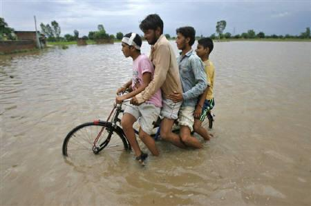 Men ride on a bicycle through a flooded road after a heavy downpour on the outskirts of Jammu Sept. 15, 2011. Tens of thousands of people in Orissa are stranded - living on roof tops or sleeping in the open with little food and water - in the worst floods to hit the area in 30 years, aid workers and officials say.REUTERS/Mukesh Gupta/Files