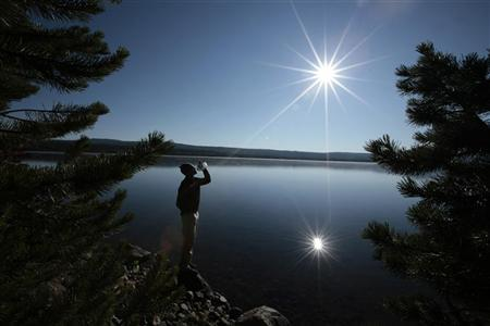 A hiker drinks from a water bottle in front of Heart Lake in the Red Mountains of Yellowstone National Park, Wyoming August 10, 2011. REUTERS/Lucy Nicholson