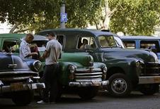 Мужчины стоят около такси в Гаване, 12 апреля 2011 года. Впервые после революции 1959 года кубинцы получат право покупать и продавать автомобили благодаря долгожданной реформе Рауля Кастро, нового шага к расширению экономической свободы на острове, где правит режим коммунистов. REUTERS/Desmond Boylan