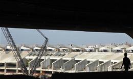 Строитель работает на участке обновления стадиона в Рио-де-Жанейро, 31 сентября 2011 года. Гладкая монорельсовая дорога, пролегающая над водами Амазонки в городе Манаус на западе Бразилии, - именно этот проект должен был символизировать все преимущества технического развития, которое обещает южноамериканской стране чемпионат мира по футболу 2014 года. REUTERS/Sergio Moraes