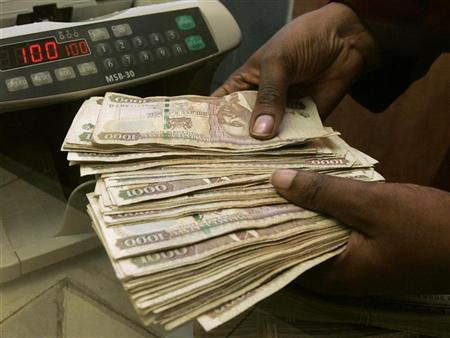 A currency dealer counts Kenya shillings at a money exchange counter in Nairobi October 23, 2008.    REUTERS/Antony Njuguna