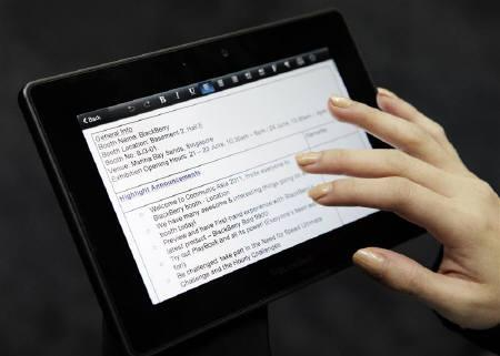 A Research In Motion (RIM) staff reads a document on her BlackBerry PlayBook tablet device during the CommunicAsia expo in Singapore June 21, 2011.  REUTERS/Tim Chong/Files