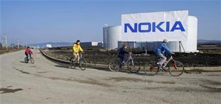 Children ride their bicycles past a billboard near the entrance of the Nokia plant in Jucu village near Cluj, about 450 km (280 miles) northwest of Bucharest February 11, 2008. REUTERS/Bogdan Cristel