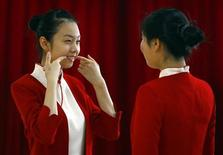 <p>A student shows another how to smile during an etiquette training class at a vocational school in Beijing January 7, 2008. REUTERS/David Gray</p>