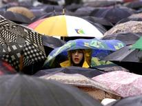 Люди стоят под зонтом в Москве, 7 апреля 2001 года. Холодная промозглая погода ненадолго уйдет из Москвы к концу текущей рабочей недели, ожидают синоптики. REUTERS/William Webster