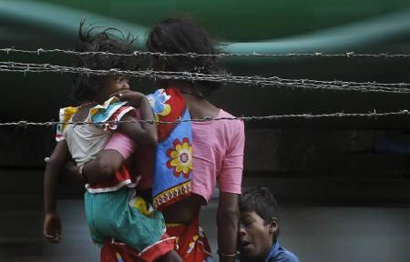 A woman, holding her children, prepares to cross a road in Mumbai May 30, 2011. REUTERS/Danish Siddiqui/Files