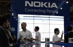 Сотрудники магазина Nokia в Сингапуре общаются с покупателями, 21 июня 2011 года. Финская Nokia выпустит свои первые смартфоны на базе Windows в текущем квартале, сказал во вторник исполнительный директор компании. REUTERS/Tim Chong
