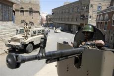Солдат, перешедший на сторону антиправительственных сил, сидит за пулеметом бронетранспортера в Сане. Фото от 3 октября 2011. Как минимум два человека погибли во вторник от минометного обстрела в столице Йемена в боях между верными президенту силами и оппозицией и еще 14 человек погибли в результате авиаударов по исламистам на юге REUTERS/Mohamed al-Sayaghi