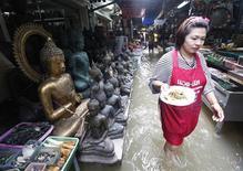 Женщина несет тарелку с едой мимо торговых рядов на залитом водой рынке в Бангкоке. Фото от 3 октября 2011. По меньшей мере 224 человека погибли с середины июля в Таиланде в результате наводнения. REUTERS/Kerek Wongsa