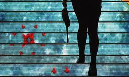 """Женщина идет по лестнице в магазине в Риме 2 августа 2011 года. Агентство Moody's во вторник понизило кредитный рейтинг Италии на три ступени, заявив, что видит """"значительное повышение"""" рисков финансирования для стран еврозоны с высокими уровнями задолженности, и предупредив о возможности дальнейшего снижения рейтинга. REUTERS/Tony Gentile"""