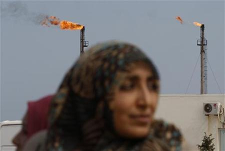 Libyan women walk past flare columns burning excess gas at the Azzawiya oil refinery in Zawiyah, 50 km (30 miles) west of the capital Tripoli March 3, 2011. REUTERS/Ahmed Jadallah