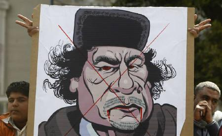 Protesters display a caricature of Libyan leader Muammar Gaddafi outside the Arab League headquarters in Cairo March 12, 2011, during an emergency meeting of the League's foreign ministers to discuss Libya. REUTERS/Amr Abdallah Dalsh