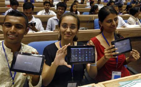 Students display Aakash, which means sky, dubbed the world's cheapest tablet computer, after its launching ceremony in New Delhi October 5, 2011. Aakash will be sold to students at the subsidised price of $35 to expand digital access in the Asian giant that lags peers such as China and Brazil in connectivity. REUTERS/Parivartan Sharma