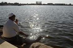 <p>A man fishes near the port of Benghazi September 9, 2011. REUTERS/Asmaa Waguih</p>