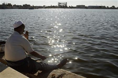 A man fishes near the port of Benghazi September 9, 2011. REUTERS/Asmaa Waguih