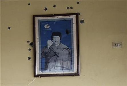 A bullet-riddled picture of Muammar Gaddafi hangs on the wall of a cafetaria at a gas station of Bou Hadi town after anti-Gaddafi fighters took control in Sirte October 3, 2011. REUTERS/Asmaa Waguih