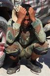 Ливийский повстанец рыдает после гибели друга в битве за Сирт. Фото от 4 октября 2011. Ливийский город Сирт, обороняемый сохранившими верность Муаммару Каддафи силами, может быть взят под полный контроль Национального переходного совета в течение двух дней. REUTERS/Esam Al-Fetori