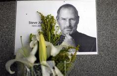 Цветы около фотографии со-основателя Apple Стива Джобса в Шанхае, 6 октября 2011 года. Стив Джобс, изменивший мир персональных компьютеров и мобильных телефонов, скончался в среду в возрасте 56 лет после многолетней борьбы с раком поджелудочной железы. REUTERS/Carlos Barria