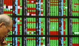 Участник фондового рынка следит за котировками в брокерской конторе в Тайпэе. Фото от 17 марта 2011. Акции компании Apple дешевеют в ходе дневных торгов на бирже во Франкфурте после того как Стивен Пол Джобс, бывший глава и сердце компании, ушел из жизни в ночь со среды на четверг после изнурительной борьбы с раком и другими проблемами со здоровьем. REUTERS/Pichi Chuang