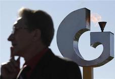 Мужчина стоит на фоне логотипа Газпрома под Ставрополем, 3 ноября 2010 года. Российский Газпром и немецкая RWE договорились, что эксклюзивность их переговоров о создании СП в электроэнергетике Европы, сохранится до конца 2011 года. REUTERS/Eduard Korniyenko