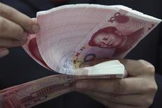 Работник отделения банка Industrial and Commercial Bank of China (ICBC) в Хуайбэе пересчитывает юани, 17 февраля 2011 года. Второй по величине российский госбанк ВТБ объявил о приеме депозитов в юанях, откликнувшись на похвалы премьер-министра Владимира Путина в адрес конкурирующей с США китайской экономики. REUTERS/Stringer