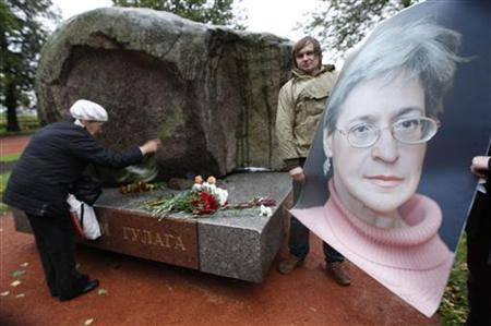 A man holds a portrait of the killed journalist Anna Politkovskaya as a woman lays flowers during a commemorative rally in St.Petersburg, October 7, 2009. REUTERS/Alexander Demianchuk