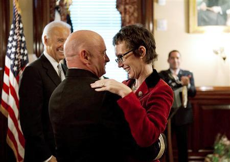 Captain Mark Kelly hugs his wife U.S. Representative Gabrielle Giffords (D-AZ) after receiving the Legion of Merit from U.S. Vice President Joe Biden during Captain Kelly's retirement ceremony in the Secretary of War Suite in the Eisenhower Executive Office Building in Washington, October 6, 2011.  REUTERS/David Lienemann/The White House/Handout