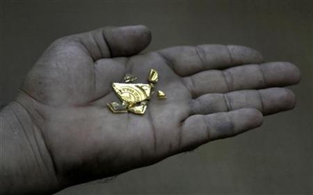 A goldsmith displays a gold nugget at a jewellery workshop in Karachi December 3, 2009.  REUTERS/Akhtar Soomro