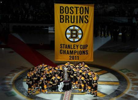 Boston Bruins players pose with the Stanley Cup trophy and their championship banner before taking on the Philadelphia Flyers in the NHL season opener hockey game in Boston, Massachusetts October 6, 2011.   REUTERS/Adam Hunger